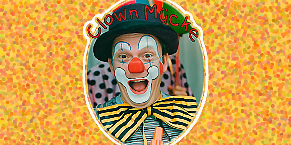 Clown Mücke lacht geschminckt und mit Hut in die Kamera