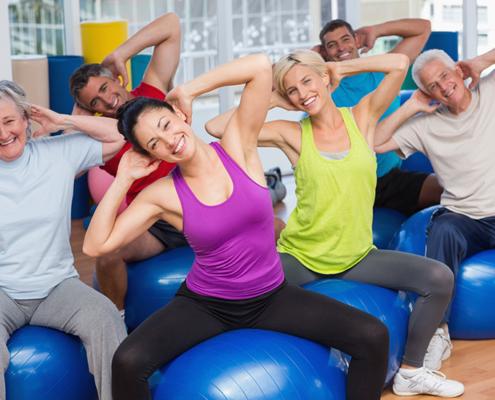 Mach mit - bleib fit! Männer und Frauen jeden Alters trainieren in einer Sporthalle