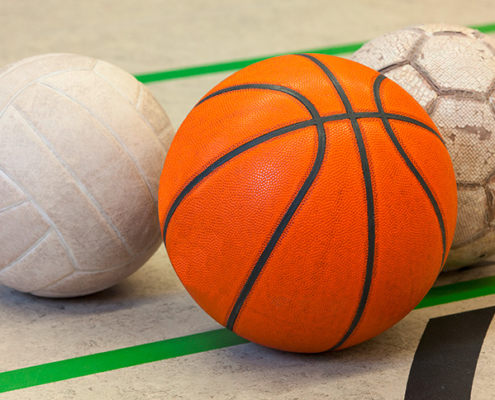 Drei unterschiedliche Bälle. Ein Volleyball, ein Handball, ein Fußball