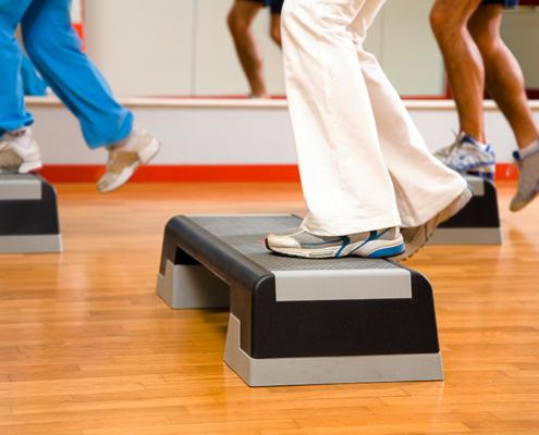 Sportler bei Step Aerobic auf dem Stepper