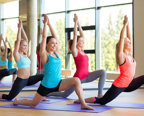 Frauen trainieren auf einer Matte in einer Sporthalle