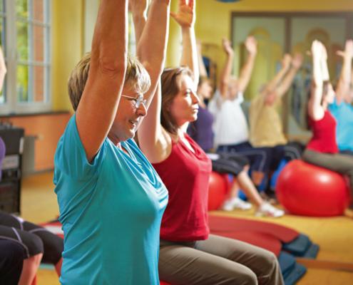 Erwachsene sitzen auf Gymnastikbälle und strecken die Arme in die Luft