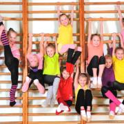 Kinder hängen an einer Sprossenwand in der Turnhalle